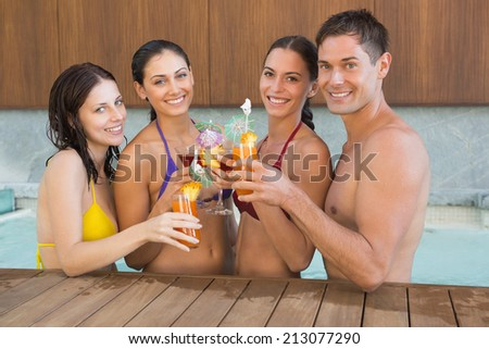 Portrait of cheerful young people toasting drinks in the swimming pool - stock photo