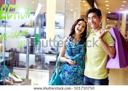 Portrait of cheerful young people with colorful shopping bags smiling at camera - stock photo