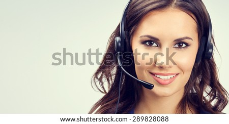 Portrait of cheerful young support phone operator or businesswomen in headset, with blank copyspace area for slogan or text. Customer service concept. - stock photo