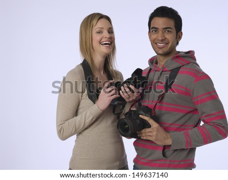 Portrait of cheerful young woman and man with digital cameras in studio - stock photo