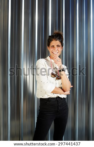 Portrait of cheerful young woman dressed in a glamorous modern clothes standing on shiny chrome background with copy space for your text message, happy teenager smiling brightly to camera in sunny day