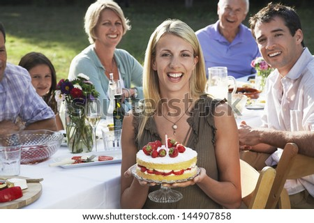 Portrait of cheerful young woman holding birthday cake with family sitting at dining table in garden - stock photo