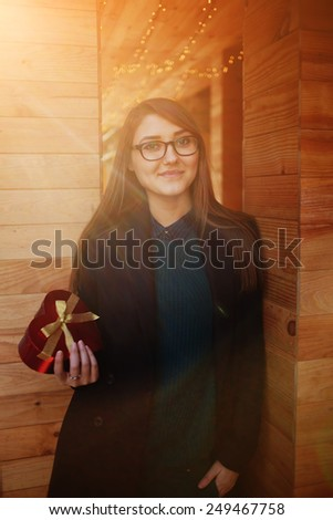 Portrait of cheerful young woman holding heart shape gift box presented by her boyfriend on Valentine's Day - stock photo