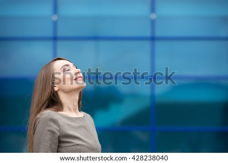 Portrait of cheerful young woman relaxing outdoors with closed eyes. Happy beautiful caucasian woman breathing fresh air on the street in summer. Copy space - stock photo