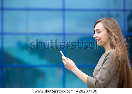 Portrait of cheerful young woman sending message on smartphone outdoors. Happy beautiful caucasian woman using mobile phone, making call, looking at screen on the street in summer. Copy space - stock photo