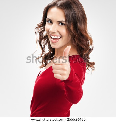 Portrait of cheerful young woman showing thumbs up gesture, over grey background - stock photo