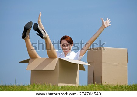 Portrait of cheerful young woman sitting in cardboard box at park with arms outstretched - stock photo