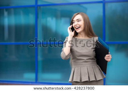 Portrait of cheerful young woman talking on smartphone and laughing outdoors. Happy beautiful caucasian woman using mobile phone, making call on the street in summer. Copy space - stock photo