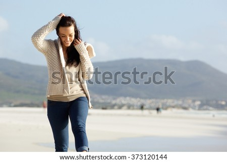 Portrait of cheerful young woman walking along a beach - stock photo