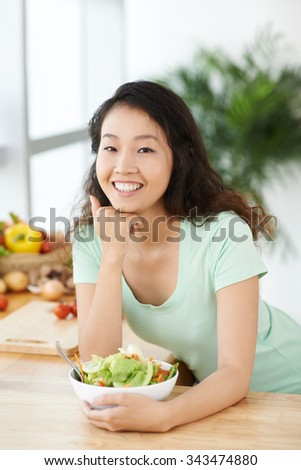 Portrait of cheerful young woman with a bowl of salad