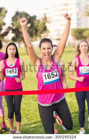 Portrait of cheering brunette winning breast cancer marathon in parkland - stock photo