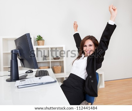 Portrait of Cheering Businesswoman At Desk In Office. - stock photo