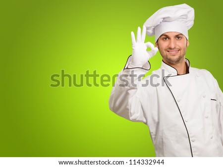 Portrait Of Chef Showing Ok Sign On Green Background - stock photo