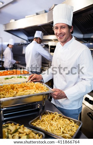 Portrait of chef standing at serving trays of pasta in commercial kitchen