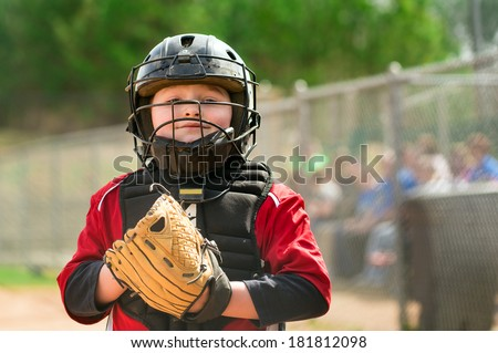 Portrait of child baseball player wearing catcher gear - stock photo