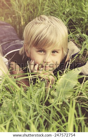 Portrait of child boy on green grass outdoors - stock photo