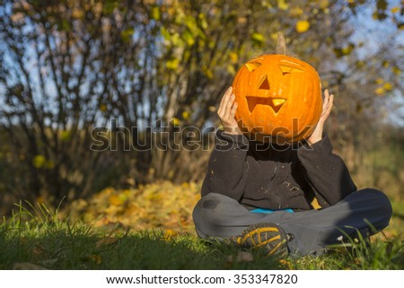 Portrait of child Boy with halloween pumpkin jack-o-lanterns in front of face, sitting on the grass, autumn garden, sunny day - stock photo