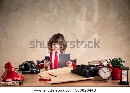 Portrait of child businessman in office. Kid holding gadgets. Communication in business concept - stock photo