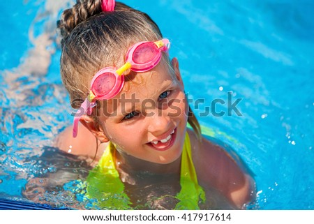 Portrait of child girl wearing googles on water slide at aquapark . Summer water holiday reacriation . Outdoor. - stock photo