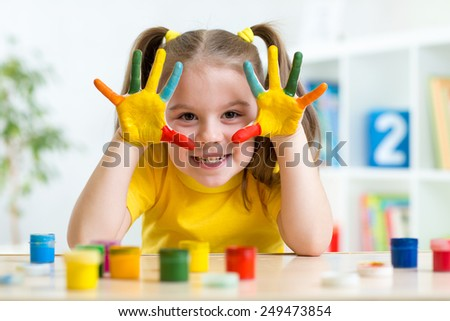 Portrait of child girl with face and hands painted at home - stock photo