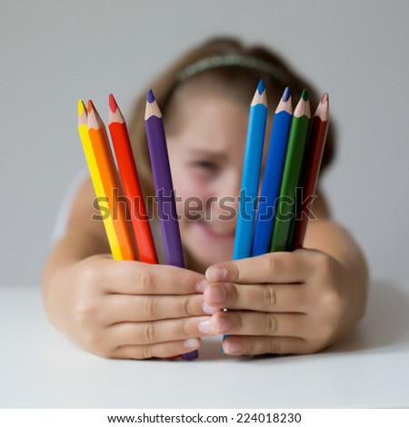 Portrait of child holding crayon before face - stock photo