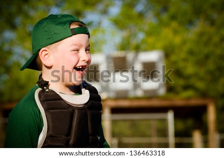 Portrait of child in catcher's gear laughing while playing baseball - stock photo