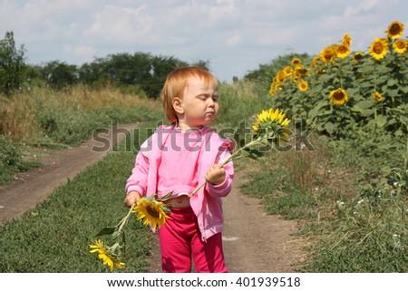 Portrait of child in sunflower field - stock photo