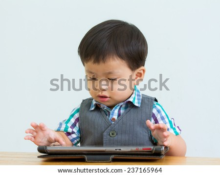 portrait of child on table in a game on a digital tablet