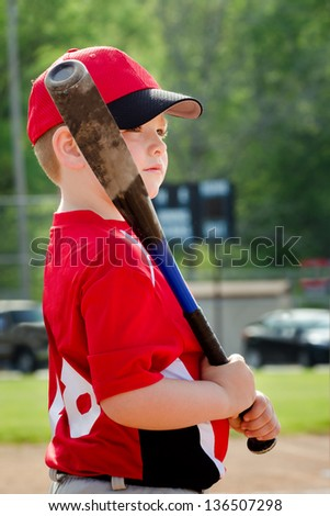 Portrait of child preparing to bat during organized league baseball game - stock photo