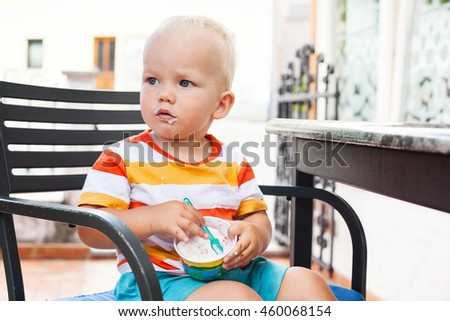 Portrait of child toddler eating ice cream at the cafe. Summertime! - stock photo