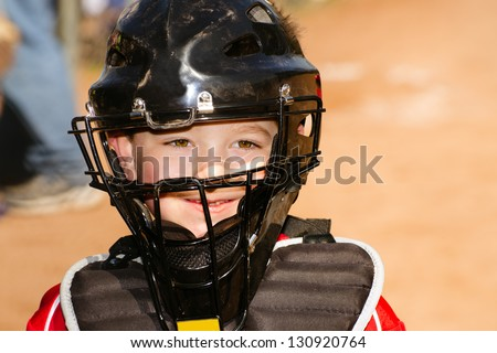Portrait of child with catcher's equipment on during baseball game - stock photo