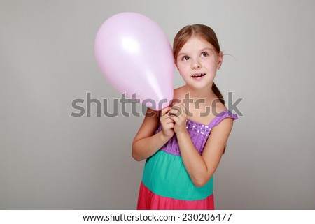 Portrait of child with cute smile in a bright sundress holding colorful balloons on a gray background