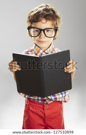 Portrait of child with rimmed glasses isolated on grey background. Child who wears plaid shirt with a book in hands - stock photo