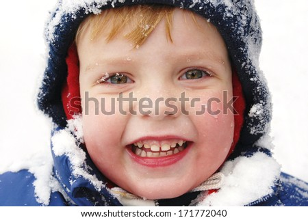 Portrait of child with snowflakes on his face - stock photo