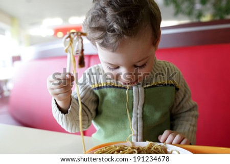 Portrait of child with spaghetti in the restaurant