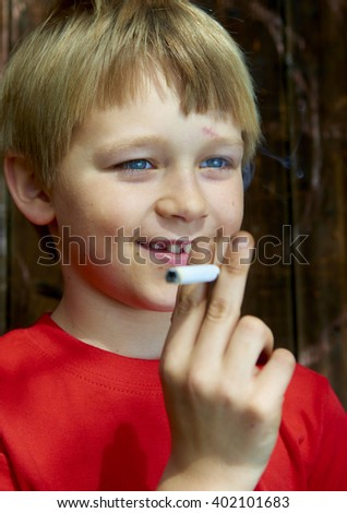 Portrait of Child young schoolboy smoking the Cigarette on the backyard