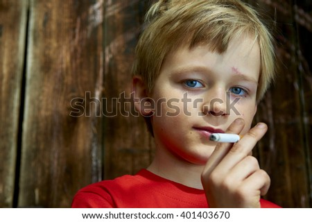 Portrait of Child young schooler boy smoking the Cigarette on the backyard. Teenager secretly smoke the Cigarette, wooden wall background, portrait