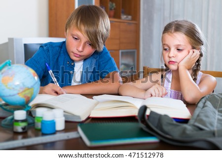 Portrait of children doing homework at the desk in domestic interior