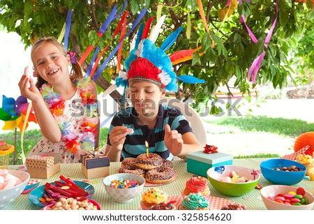 Portrait of children dressing up in fancy dresses at a colorful birthday party in a home garden, eating with candle on cake, with joyful expressions outdoors lifestyle. Kids activities and fun. - stock photo