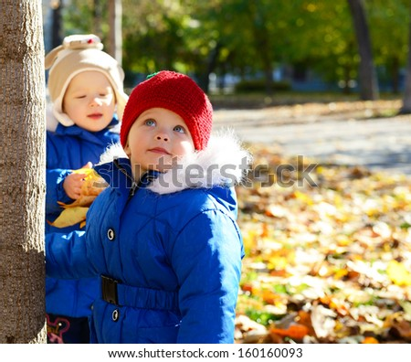 Portrait of children have fun outdoor. Little girls playing with leaves in autumn park