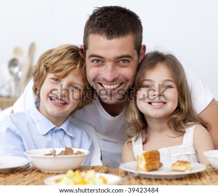 Portrait of children having breakfast in kitchen with father - stock photo