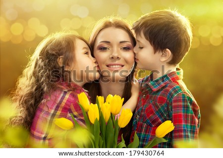 Portrait of children kissing her mother with flowers. Spring, March 8, International Womens, Mothers day, family holiday - stock photo