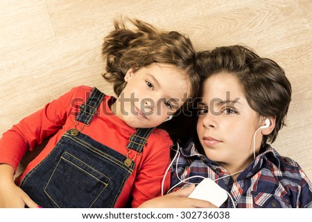 Portrait of children listening to music with headphones stretched on a parquet floor at home - stock photo