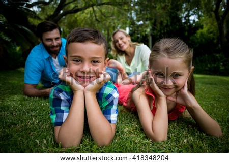 Portrait of children lying with head in hands against parents sitting in yard - stock photo