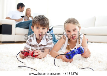 Portrait of children playing video games lying on the floor - stock photo