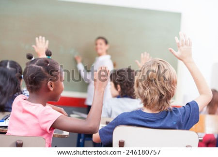 Portrait of children raised their hands in a multi ethnic classroom.