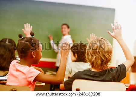 Portrait of children raised their hands in a multi ethnic classroom. - stock photo