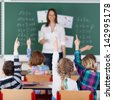 Portrait of children raised their hands in the classroom - stock photo