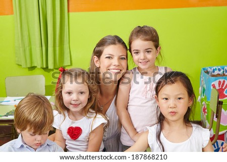 Portrait of children with happy nursery teacher in a kindergarten - stock photo