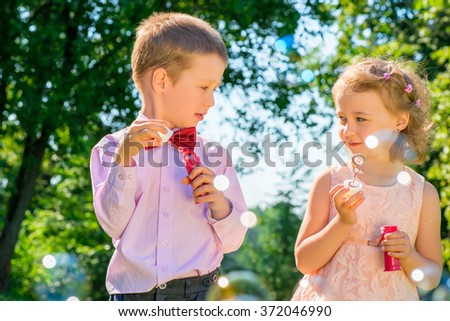 portrait of children with soap bubbles outdoors in the park - stock photo